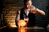 Close-up. Barman professionally pours cocktail to smoky glass sprinkles to it and make fire.