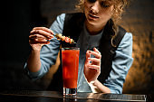 close-up of female barman carefully decorates cocktail Bloody Mary by canapes.