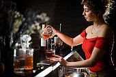 Pretty woman in red blouse pours cocktail from mix bowl into glass