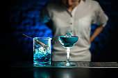 Close-up blue glass and mixing cup with blue cold cocktail stand on bar counter