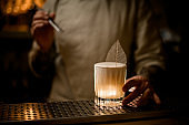 old fashioned glass of drink with foam decorated with leaf stands on bar counter