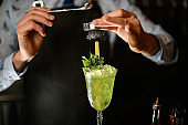 Professional bartender decorates by powder icy green cocktail in glass.