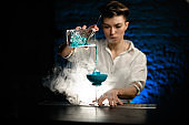 Woman bartender masterfully pours blue cocktail from mixing cup into glass at smoky bar
