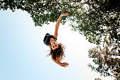 Bottom view of cheerful woman in the air against blue sky and green trees.