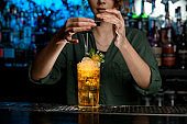 Young woman bartender carefully decorate by powder glass with cocktail.