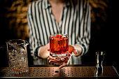 close-up old-fashioned glass with cocktail decorated with red pepper in woman hands at bar