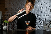 Lady bartender pours ready-made cocktail into glass.
