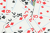 Mixed playing cards background. Assorted play cards backdrop. Many miscellaneous jumbled playing cards surface.