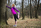 Woman athlete stretching out in nature