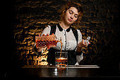 female bartender pours alcoholic drink from decanter into glass.