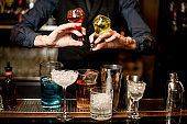 bartender holds bottles with liquor and adds it to glass with cocktail
