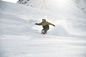 Snowboarder in anorak rides on a snowboard in mountains