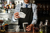 bartender in black apron holds glass and steel shaker at bar.