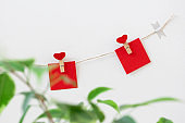 Garland with heart clothespins and red paper note hanging on rope twine on white wall, horizontal. Decorations for Valentine's day or wedding party, outside. Green leaves defocused