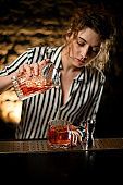 barman lady carefully pours ready-made cold cocktail from mixing cup into glass