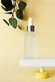 Facial serum bottle standing on abstract pedestal on pastel yellow background with copy space and defocused eucalyptus leaves, front view. Skincare beauty product mockup, vertical