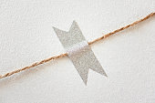 Silver glitter decorative tape on white textured background. Close-up scrapbook details