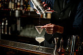 bartender pours drink through sieve into glass