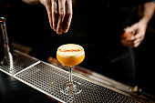 Male bartender sprinkles alcohol drink on a bar counter