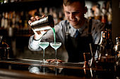 Smiling young barman pours ready-made cocktail from shaker into glass.