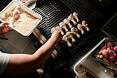 male chef accurate puts marinated chicken legs to barbecue grill
