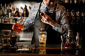 Professional barman using beaker pours drink into glass shaker