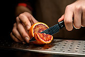 close-up bartender cuts slice of citrus with knife