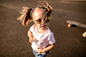 Portrait of little cute girl in sunglasses with two ponytails.