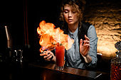 Woman bartender set fire flame over glass with cocktail.