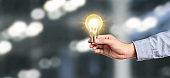Hand of holding illuminated light bulb. innovation inspiration concept