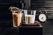 Whipped instant coffee. New popular food and drink trend. One glass of Korean Dalgona coffee with oat milk on dark background