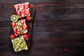 Healthy toasts with kiwi, strawberry and ricotta