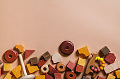 Kids toys. Wooden cubes, cars, pyramid tower and teether on a peach background. Copy space.