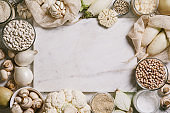 White vegetables and mushrooms, rice, quinoa, legumes, white peppercorns, coconut oil around a white marble cutting board on a white background. Healthy eating and the concept of clean eating.