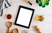 Tablet with blank screen and different kitchen and cooking utensils on whie wooden table. Culinary blog, recipe template, online cooking courses
