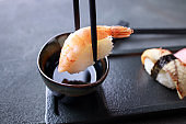 Chopsticks dipping prawn nigiri sushi into sauce