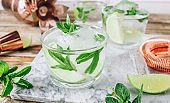 Lemonade, infused water or Mojito cocktail making. Mint, lime, ice ingredients and bar utensils.