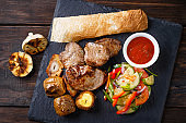 Grilled meat with potatoes and vegetable salad