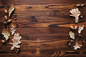 Fall oak leaves and acorns border on wooden table