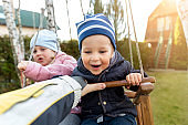 Two cute adorable playful caucasian siblings boy girl child enjoy having fun swinging wooden swing at backyard together with father. Little toddler brother and sister laughing at playing outdoors