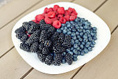 White ceramic plate with assorted sweet juicy organic seasonal berries for snack. Ripe tasty fresh raspberry, blackberry and blueberry summer mix for breakfast morning. Healthy vitamin nutrition diet