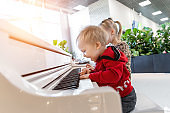 Adorable cute caucasian little toddler boy having fun playing big white piano in mall indoor. Funny happy small child enjoy singing and making loud music with instrument. Happy childhood concept