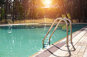 Big luxury empty rectangular swimming pool with clean blue water and ladder at tropical forest beach resort at sunrise morning light and nobody outdoors. Healthy leisure lifestyle travel and exercise