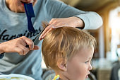 Close-up young adult caucasian mother making haircut fot cute adorable son toddler boy at home due quarantine and lockdown. Mom cutting hair of child with scissors and hairbrush