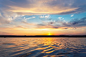 Beautiful dramatic scenic bright vibrant blue to red warm sunset evening time landscape panorama with cloudscape reflection on ripple water surface of lake or river. Horizon coast line on background