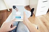 Man Voting Online Sitting at Home Using Digital Tablet.