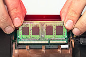 Engineer makes dismantling of RAM for disassembling and repairing a laptop.