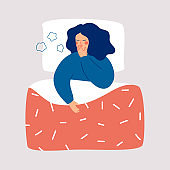 Young woman is lying in the bed and coughing.