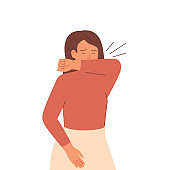 Sick woman sneezes and coughs covering her mouth with her elbow.