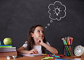 Little girl studying in front of blackboard.back to school concept.